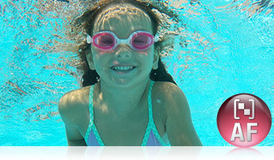 Underwater photo of a girl in pink goggles shot with the COOLPIX S33 and the Face Priority AF icon inset