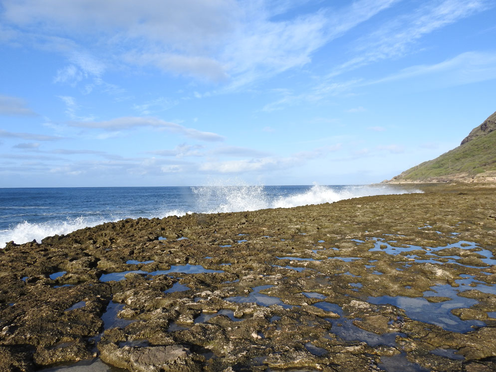 Zoom slider photo of a rocky shoreline with waves hitting it and a blue sky, wide shot