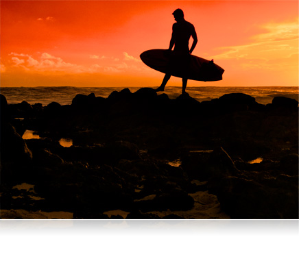 Silhouette photo of a man with a surfboard standing on the jetties