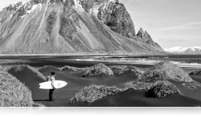 Black and White photo of a surfer at a rocky shoreline with his surfboard