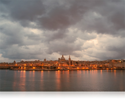 landscape photo of a waterfront city with clouds, in low light with city lights on
