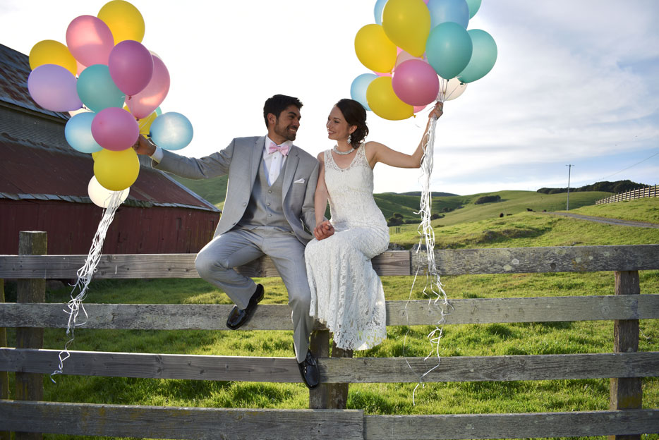 Nikon D3400 photo of a bride and groom sitting on a fence holding colorful balloons