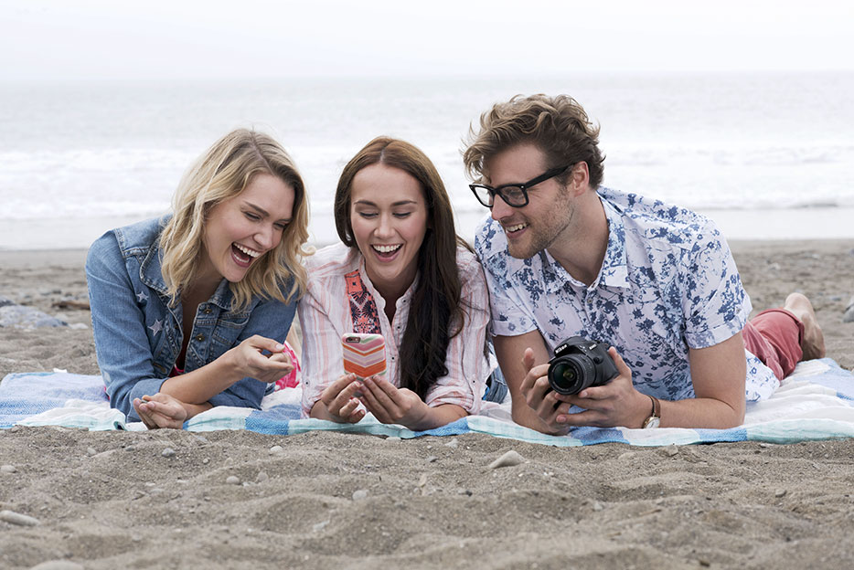 Nikon D3400 photo of two women and a man on a beach blanket looking at photos on a smartphone