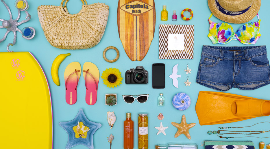 Photo of summer fun items, including beach toys and the Nikon D3400 and a smartphone showing the small size of the camera