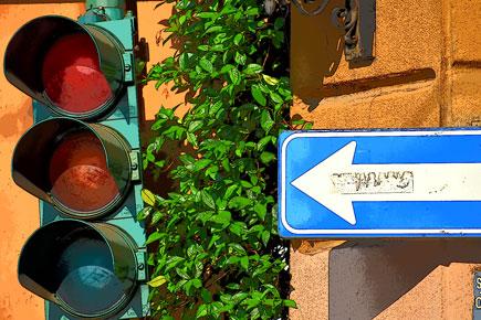 Nikon D5600 DSLR photo of a street sign and streetlight against an orange brick wall