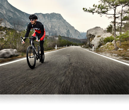 D500 photo of a mountain biker riding on a road with a mountain in the background
