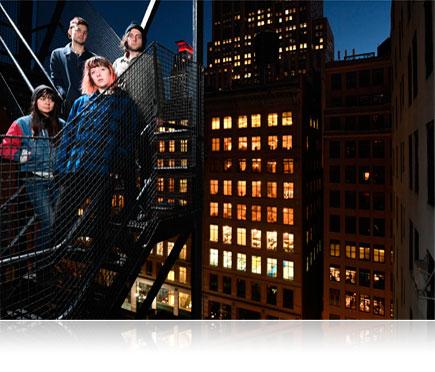 Fotografia da D500 de quatro pessoas em uma saída de emergência com uma cena da cidade à noite ao fundo