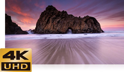 D500 photo of a low light photo of a rocky ocean shoreline with the 4K UHD logo inset
