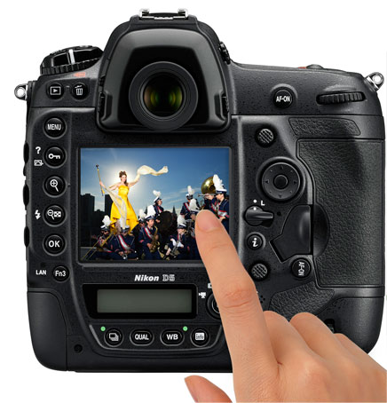 Photo of the rear of a D5 DSLR with an image of a woman leading a marching band and a hand touching the LCD showing touchscreen functionality