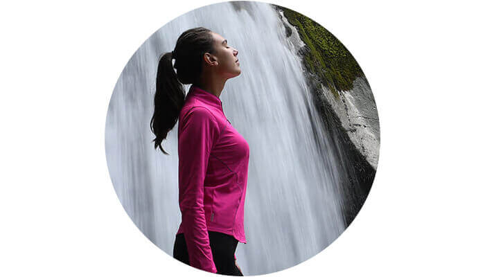 D7500 photo of a woman in a pink sweater with a waterfall behind her