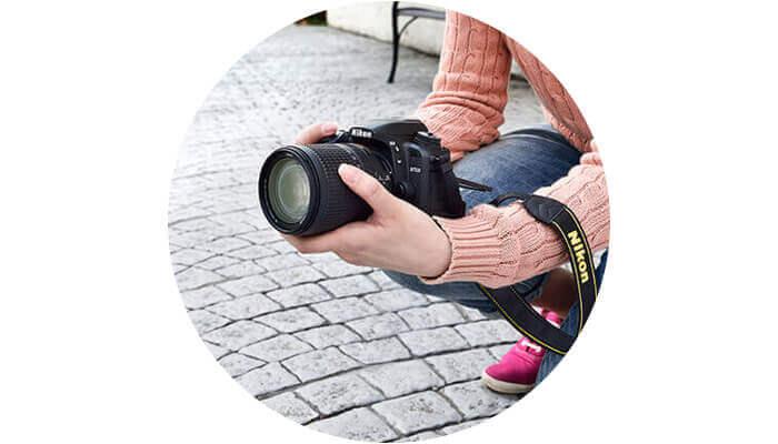 Foto de una mujer arrodillada sosteniendo una D7500 en sus manos