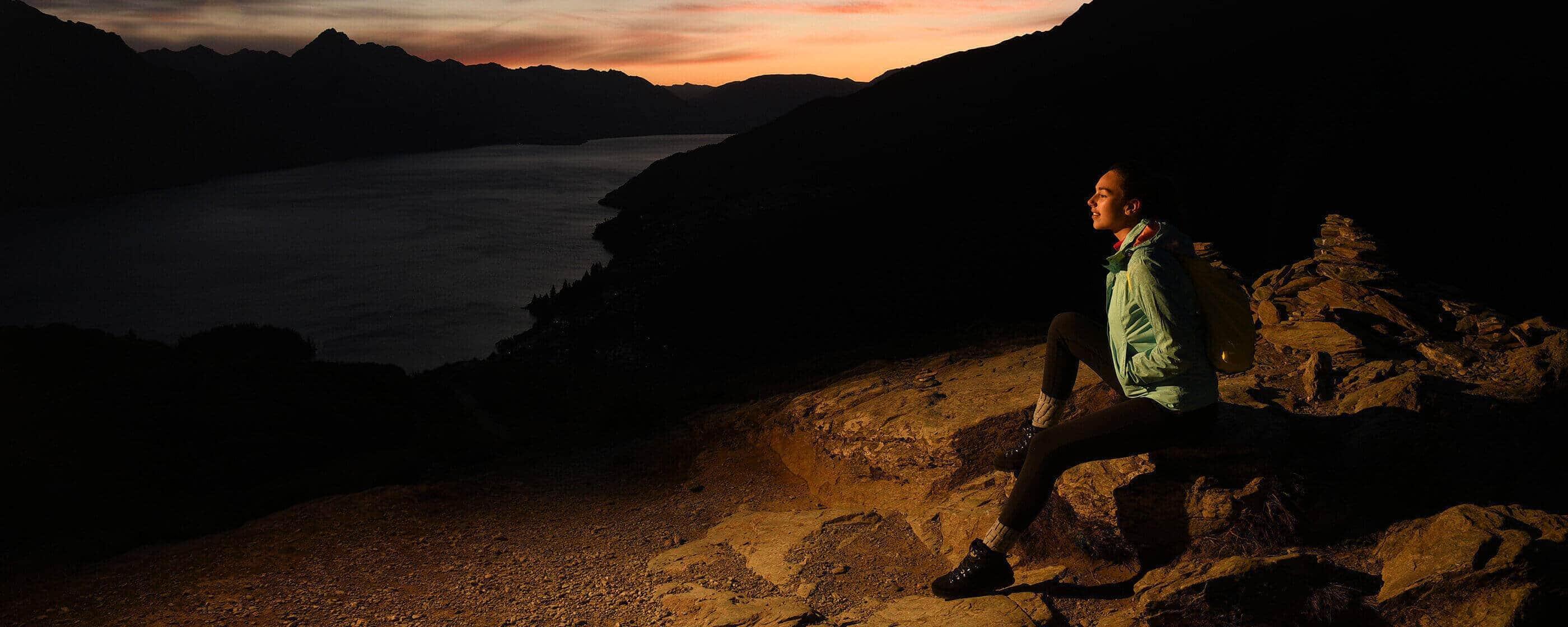 Foto de una persona sentada sobre rocas con poca luz