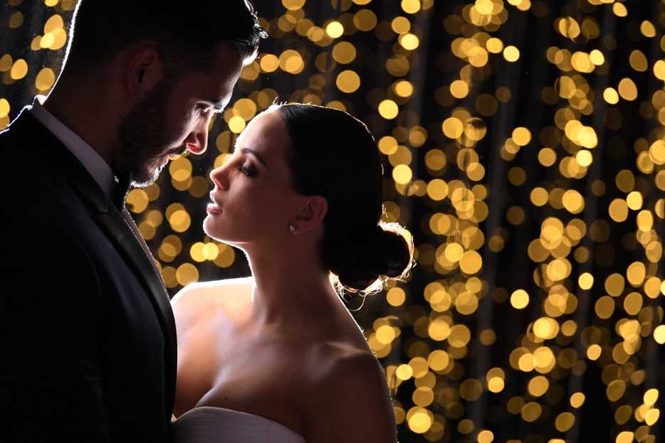 D850 DSLR photo of a bride and groom with bokeh lights in the background
