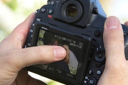 Photo of a photographer's hands on the D850 using the touchscreen LCD