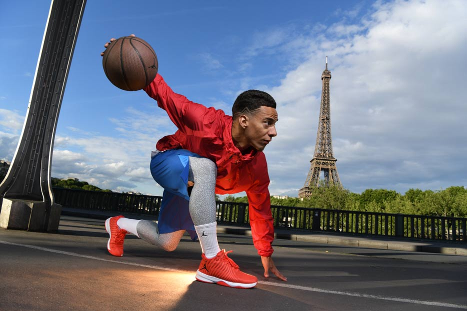 D850 DSLR photo of a basketball player kneeling with the ball in his hand and the Eiffel Tower in the background