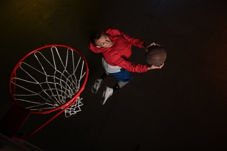 D850 DSLR photo of a basketball player jumping for a dunk in low light