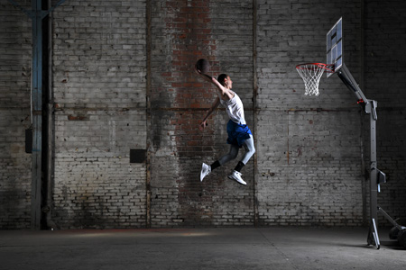 D850 DSLR photo of a basketball player in air dunking the basketball