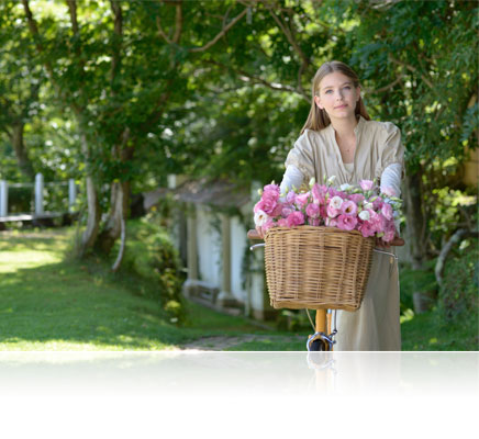 Nikon D610 photo of a woman in a garden with flowers in a basket on her bicycle