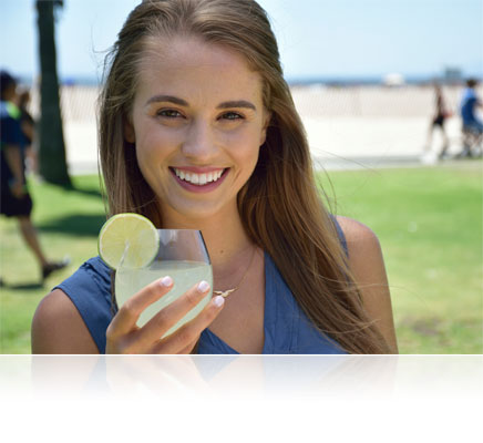 Nikon D5300 portrait of a woman holding a drink in her hand, outdoors with the beach in the background