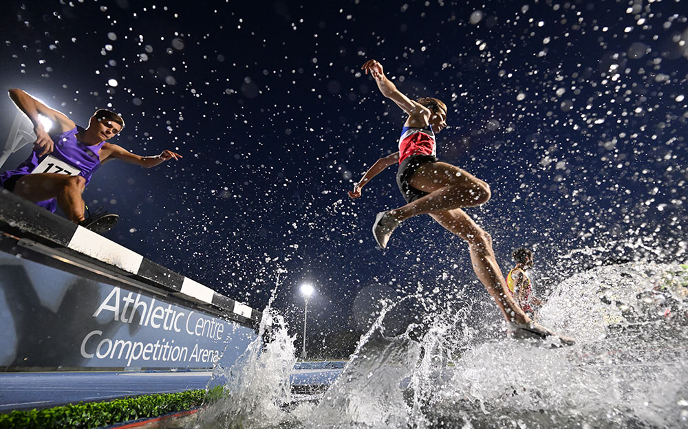D6 DSLR photo of runners jumping over water splashing