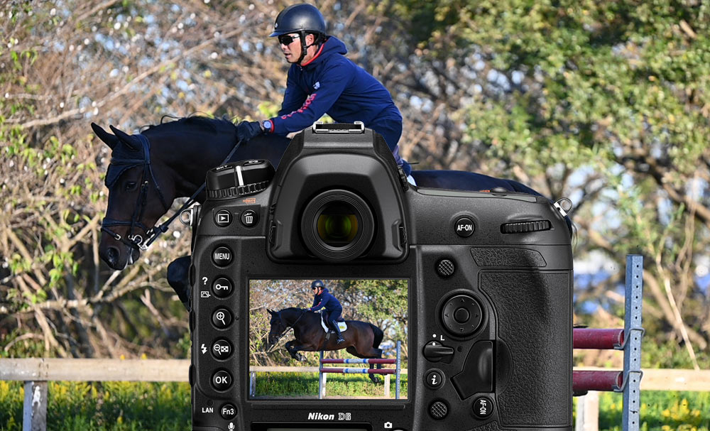 D6 DSLR photo of a horse jumping on a steeplechase course, with the camera body overlayed in front of the image, and the photo on the LCD