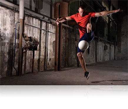 Photo of a soccer player in a run down building kicking a ball in air, lit with the Nikon SB-500 Speedlight flash