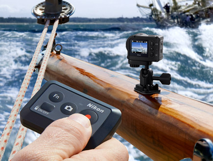 Photo of the KeyMission 170 mounted on a boat railing and a hand holding the ML-L6 remote control