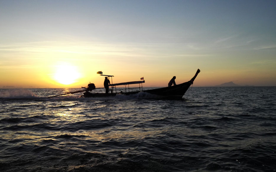 photo of two people on a boat in silhouette, shot at sunset