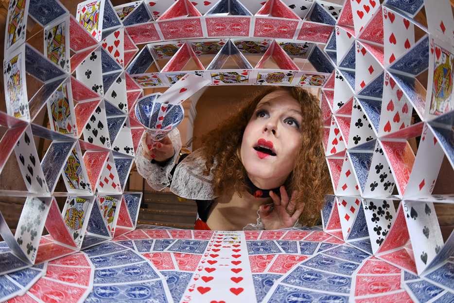 Photo of a woman and a house of cards, shot with the AF-S Fisheye NIKKOR 8-15mm f/3.5-4.5E ED lens