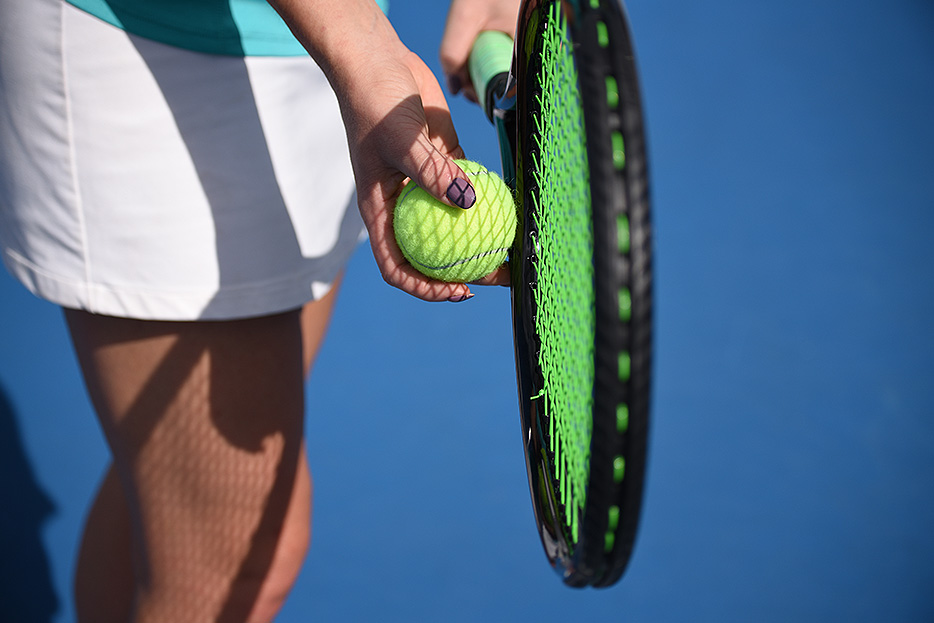 AF-P NIKKOR 70-300mm f/4.5-5.6E ED VR photo of a woman's hands holding a tennis ball and racket