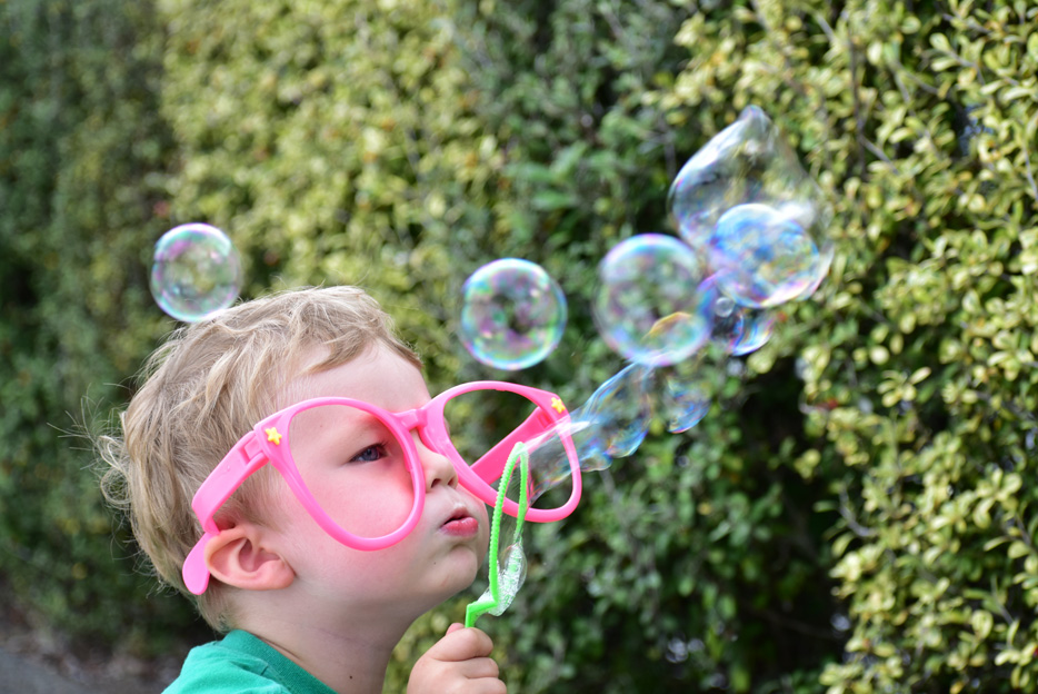 Photo of a little boy blowing bubbles, taken with the AF-P DX NIKKOR 70-300mm f/4.5-6.3G ED lens