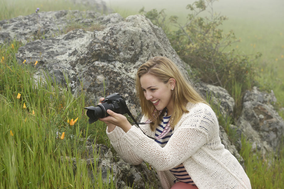 Photo of a woman shooting flowers using the AF-P DX NIKKOR 18-55mm f/3.5-5.6G VR lens on a Nikon DSLR