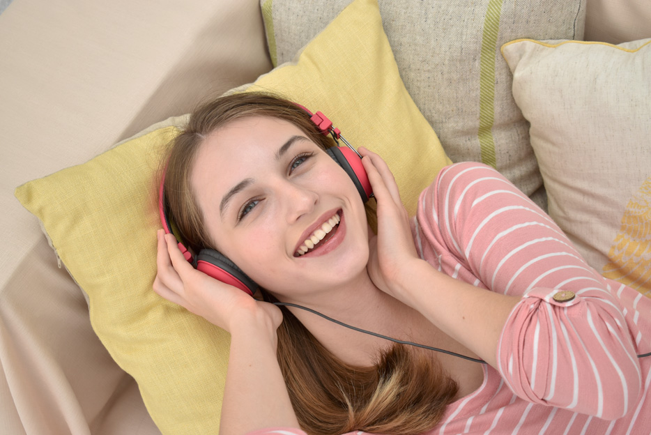 Photo of a young woman with headphones smiling at the camera, taken with the AF-P DX NIKKOR 18-55mm f/3.5-5.6G VR lens