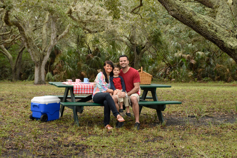 AF-S NIKKOR 50mm f/1.8G photo of a mom, dad and son on a picnic table under the trees
