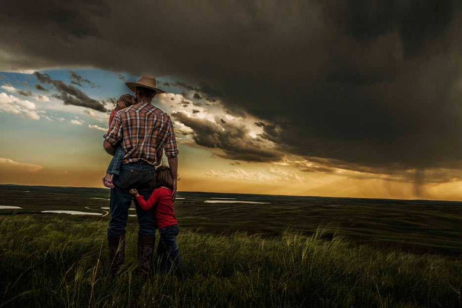 Photo of a cowboy with two kids under a cloudy sky, shot with the AF-S NIKKOR 35mm f/1.4G lens