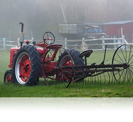 Photo shot with the AF VR Zoom-NIKKOR 80-400mm f/4.5-5.6D ED lens of farm equipment on a lawn in the fog
