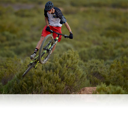 Photo of a mountain bike rider in air with green bushes in the background, shot with the AF-S NIKKOR 500mm f/4E FL ED VR lens
