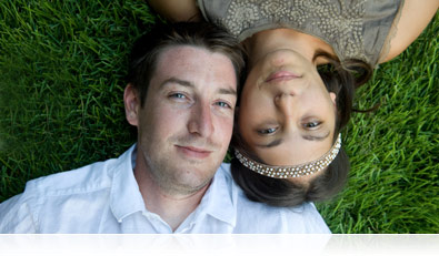 Overhead portrait of a young couple lying in the grass.
