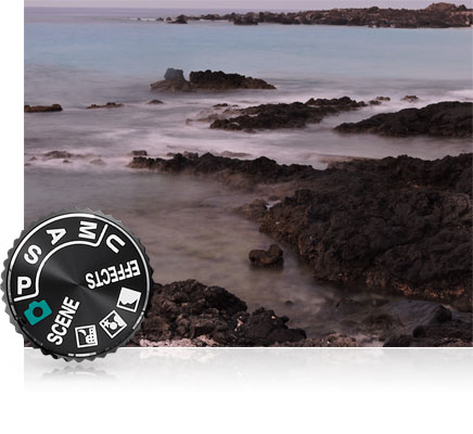 Photo of rocks and water at the seashore and the mode dial of the camera inset