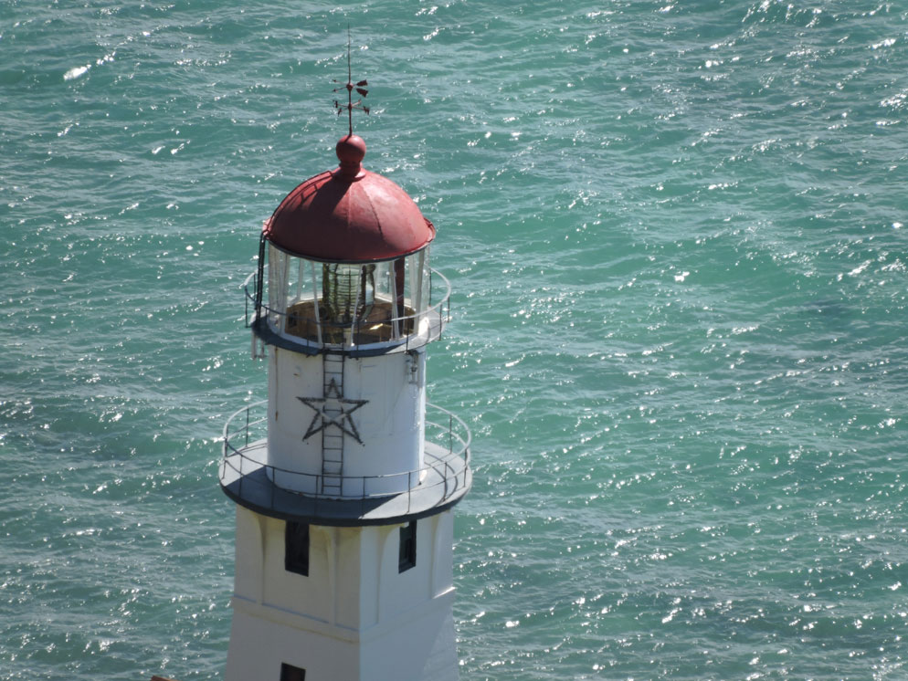 zoom slider - close up view of the top of the lighthouse and the water beyond