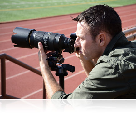 Photo of a man with the Nikon 1 V3 held up to his eye, and the camera on a tripod, shooting track and field