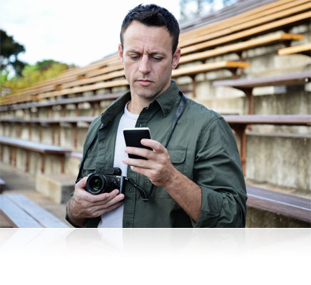 Photo of a man with the Nikon 1 V3 in his hand, looking at an image in his smartphone