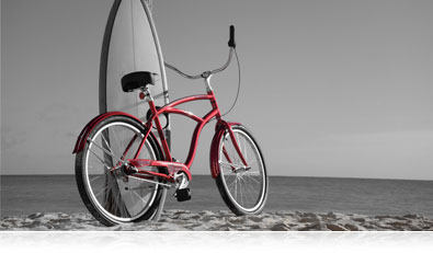 Nikon 1 V3 photo of a bicycle and surfboard on the beach, in selective color