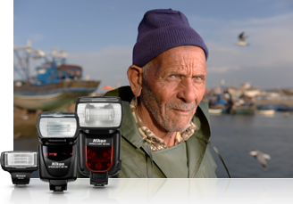 Image of three Speedlights clustered in front of a photo of an old man near the sea, with a harbor in the background