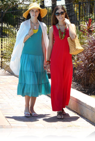 Photo of two women in sundresses smiling on a sidewalk
