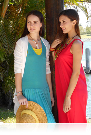Photo of two women in sundresses in the shade beneath a palm tree