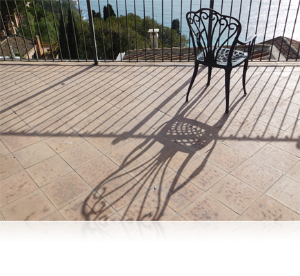 COOLPIX S7000 photo of a chair, fence and their shadows on a tiled terrace