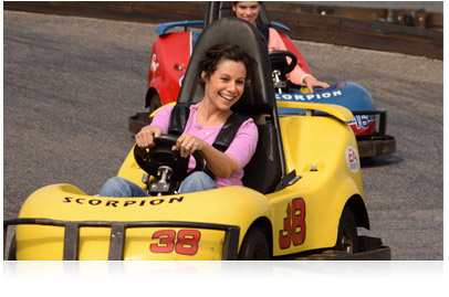 Photo of girl in yellow go-cart with girl in red go-cart following, taken with Nikon D3200 HD-SLR