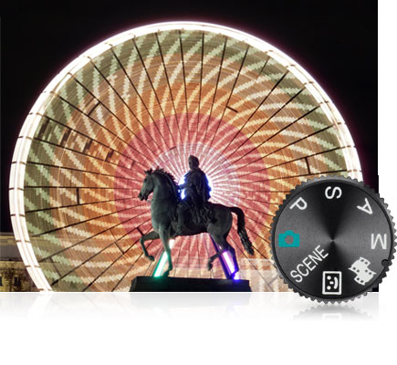 COOLPIX S9900 photo of a statue with a ferris wheel in the background in motion and the mode dial inset