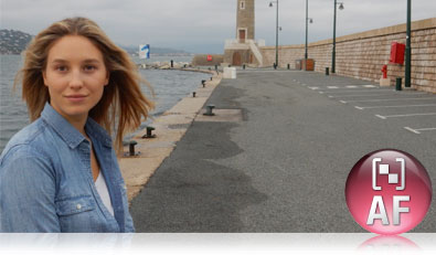 Photo of a woman on the edge of the frame, on a pier, with the Target Finding AF icon inset